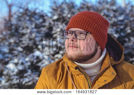 Portrait of a smiling young man in warm clothing on sunny winter day