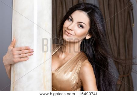 beautiful fashionable woman near the column