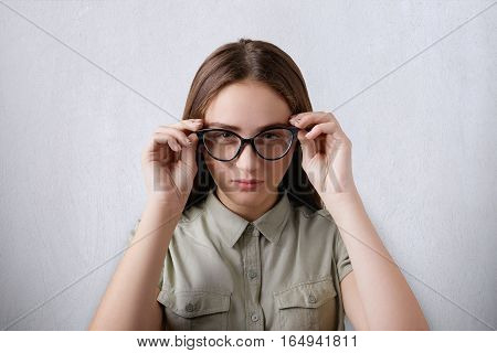 A portrait of beautiful girl wearing shirt having long hair isolated over grey background wearing big glasses touching her glasses with her hands having a confident and clever look directly at camera