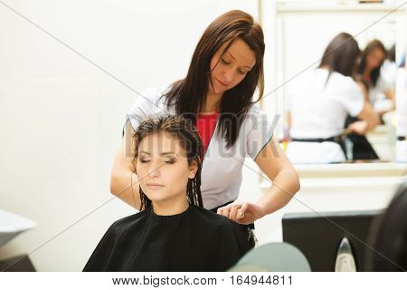 Haircare relaxation and hairstyling concept. Woman sitting in black cape getting her hair cut by lady hairdresser in beauty salon