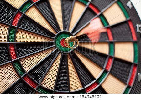Wedding rings on a dart board hitting bulls eye