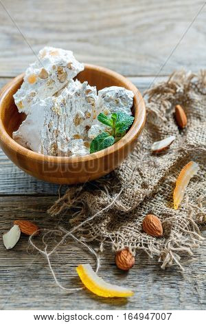 Sweet Nougat With Almonds And Candied Fruit In A Wooden Bowl.