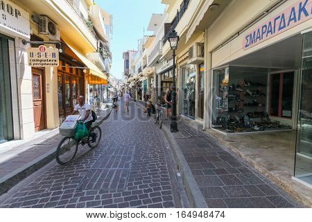 Rethymnon, Island Crete, Greece - June 23, 2016: A deliveryman of pizza on the bicycle is on the narrow street of Rethymnon (part of Old Town)