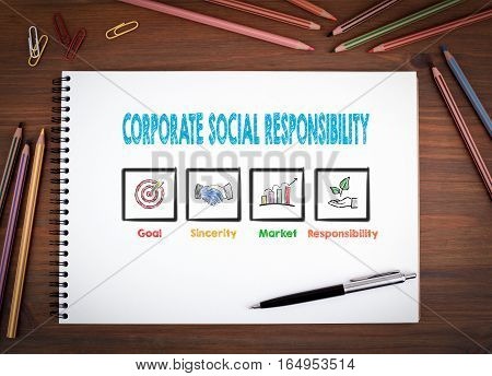 Corporate Social Responsibility. Notebooks, pen and colored pencils on a wooden table