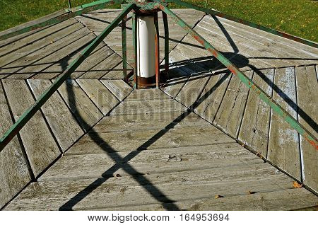 The support arms of an old vintage merry-go-round cast shadows on the wooden base.