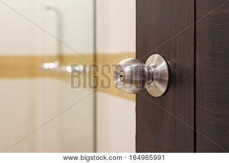 Stainless Doorknob On Wooden Door
