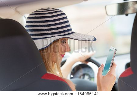 Distracted driver. Young attractive woman using mobile phone texting or read message while driving the car.