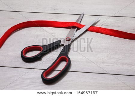 Scissors with red handles cut red tape. Red tape is lying on wooden background.