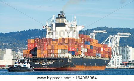 Oakland CA - January 01 2017: Tugboat AHBRA FRANCO at the stern of cargo ship SEASPAN FELIXSTOWE assisting the vessel to maneuver into the Port of Oakland.