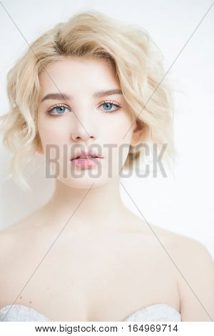 Woman with white hair in a wedding dress. Young blonde woman with blue eyes. Portrait of a beautiful blonde girl. Fashion model. Woman with perfect skin. Nude makeup. Fashion photography concept