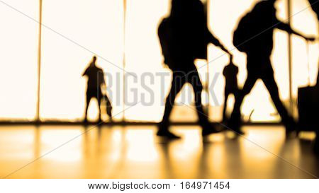Passengers going to boarding with baggage in front of window in airport, silhouette, warm, wide angle