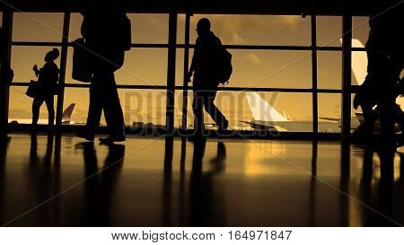 Travellers with suitcases and baggage in airport walking to departures in front of window, silhouette, warm, orange
