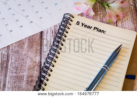 5 Year Plan Motivational business concept on notebook with calendar on wooden board