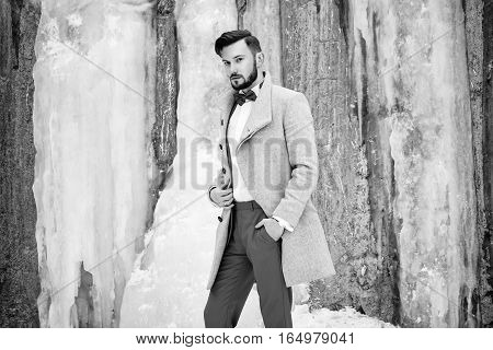 Outdoor portrait of handsome man in gray coat. Fashion photo. Beauty winter style. Black and White