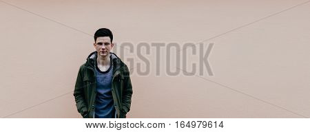 Young beautiful man in jacket on the pink wall background, photo with place for text or other/