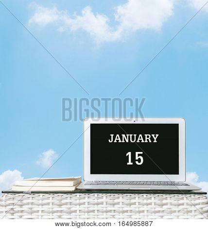Closeup computer laptop with january 15 word on the center of screen in calendar concept on blurred wood weave table and book on blue sky with cloud textured background with copy space