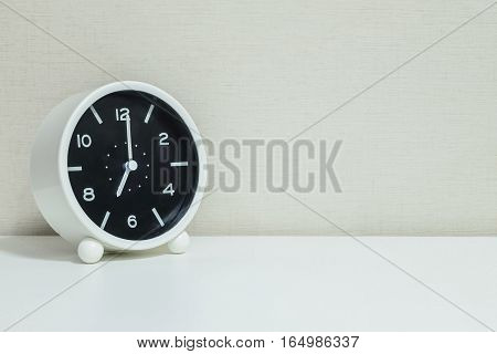 Closeup black and white alarm clock for decorate in 7 o'clock on white wood desk and cream wallpaper textured background with copy space
