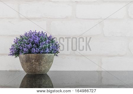 Closeup artificial purple plant on pot for decorate on black glass table and white brick wall textured background with copy space