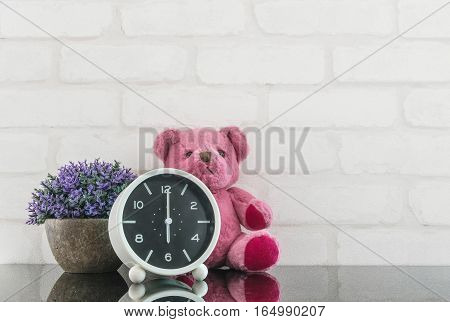 Closeup black and white alarm clock for decorate in 6 o'clock with bear doll and plant on black glass table and white brick wall textured background with copy space