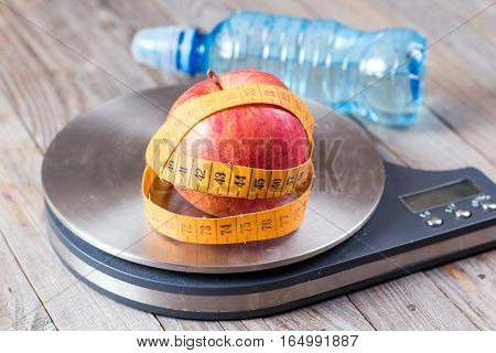 Measuring tape wrapped around a apples on wooden background