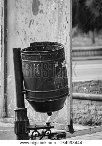Metal trash can on the street in black and white colors