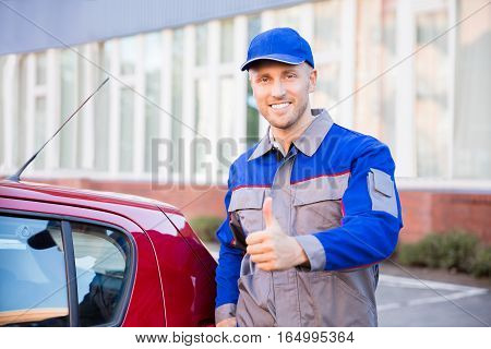 Portrait Of A Happy Young Man Standing Near Car