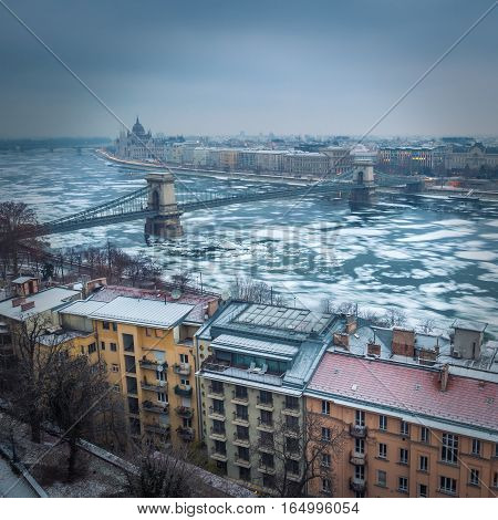 Budapest Hungary - Panoramic skyline view of the Szechenyi Chain Bridge on the icy River Danube with Parliament and Bazilika at background on a winter morning