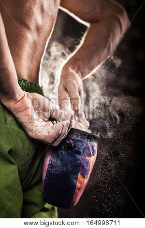 Climber man coating his hands in powder chalk magnesium and preparing to climb indoor close-up