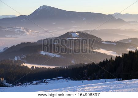 Skiing park Kubinska Hola; Western Tatras. Slovakia. View from the ski slopes on snow covered and foggy valley on the background mountain peaks. Slovakia. People skiing. Travel destination for winter vacations .