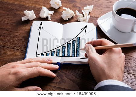 Close-up Of Businessperson Drawing Graph In Notebook On Wooden Desk