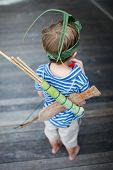 Back view of 5 years old bow with wooden sword, bow and arrows