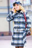Beautiful young blond in a coat talks on phone. Photography for fashion brand Catalog clothes poster