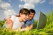 image of computer technology  - Happy couple on a laptop computer outdoors - JPG
