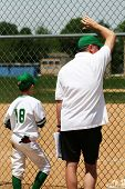 foto of little-league  - player watching the baseball game beside the coach - JPG