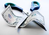 foto of depreciation  - Scissors cutting through dollar note on white background - JPG
