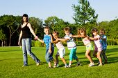 stock photo of summer fun  - Teacher with kids walking to the city park - JPG