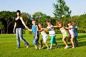stock photo of summer fun  - Teacher with kids walking to the city park - JPG
