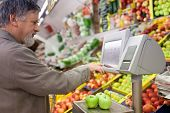 Handsome senior man shopping for fresh fruit in a supermarket (shallow DOF, sharp focus on the apple