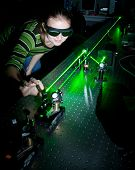 stock photo of laser beam  - female scientist working with lasers while doing research in a quantum optics lab - JPG