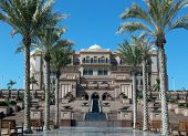 Majestic arabian palace. Alley with benches and rows of palms.