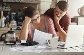 Young Stressed Caucasian Couple Facing Financials Troubles, Sitting At Kitchen Table With Papers, Ca poster