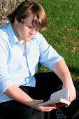 Teen Boy Reading  Outdoors poster