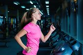 Attractive Fitness Girl Running On Machine Treadmill. Pretty Girl Doing Workout At Modern Fitness Gy poster