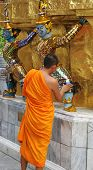 Monk Inspects A Statue At The Grand Palace, Bangkok, Thailand - Travel And Tourism. poster