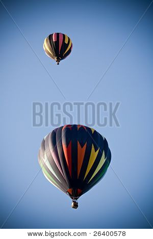 hot air balloons - two colorful balloons flying high in the clear blue sky, added vignetting