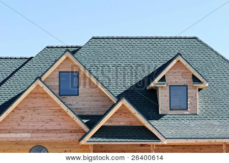 roofing architecture of a brand new home, closeup with blue sky background