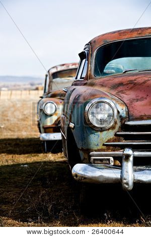 vintage car - two vintage cars abandoned on a field in rural wyoming. vertical version.