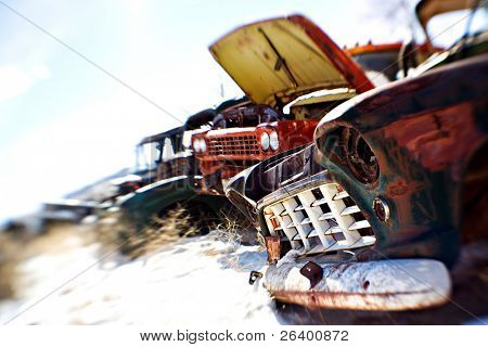 old cars in the snow at a rural junkyard. shot with a lensbaby - limited depth of field with focus on front grill. legal note - license plate heavily modified.