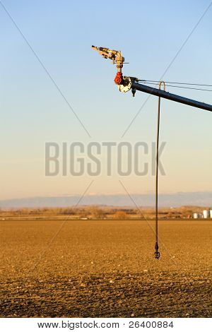 agriculture - modern automated irrigation system, closeup on end of arm with two sprinklers. Blue sky, late sun.