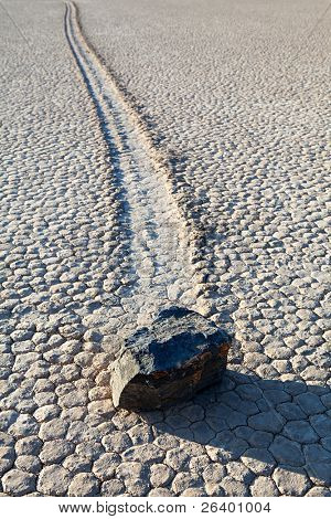 Death Valley National Park - California. Racetrack Playa with a rock and trail on dry lake bed.